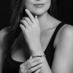 A black-and-white image of a woman wearing a bracelet.
